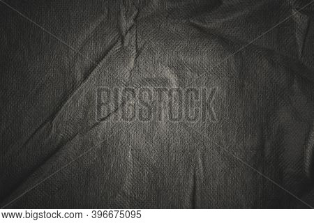 Background With Black Crumpled Sheet Of Fabric With Vignetting.
