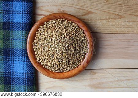 Flat Lay View Of A Wooden Bowl Full Of Malted Barley Grains, A Main Ingredient In Beer Brewing And W