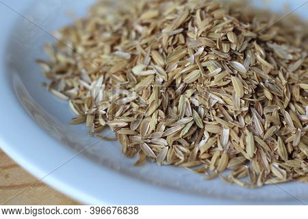 A Pile Of Rice Hulls (husks) In Close Up On A White Plate On A Wooden Table. Husks Are A Waste Produ
