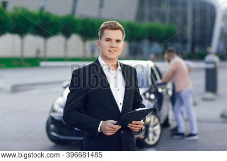 Close-up Portrait Of A Young Car Dealer In A Business Suit. Behind Him, A Young Couple, A Man And A
