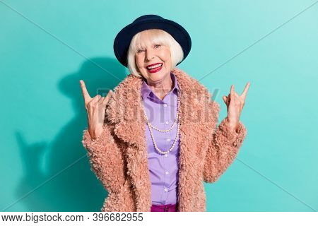 Photo Of Funky Adorable Old Woman Dressed Vintage Outerwear Cap Showing Hard Rock Sign Isolated Turq