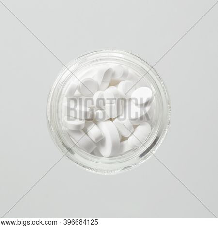 Different White Medical Pills In A Glass Jar