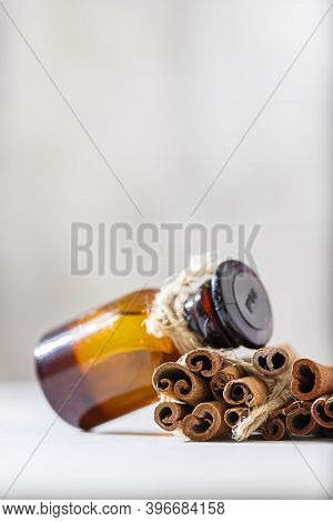 Cinnamon Essential Oil In A Bottle And Cinnamon Sticks On A Light Concrete Background. Spa Concept.