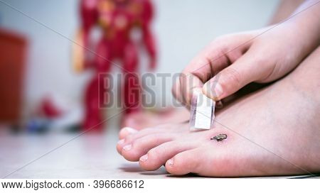 Child Putting Bandage Under Foot Wound, Band Aid Over Wound With Scab