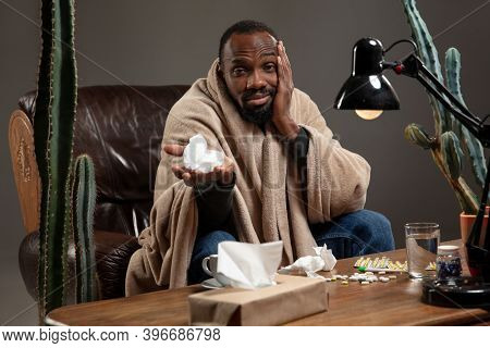 Terrible Headache. African-american Man Wrapped In A Plaid Looks Sick, Ill Sitting On Armchair At Ho