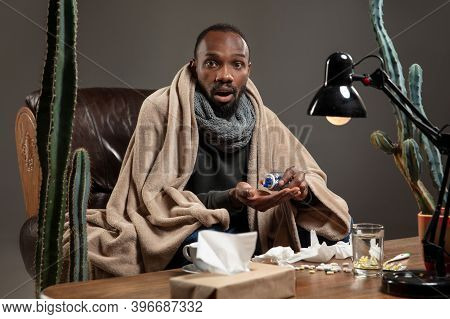 Pills, Drugs. African-american Man Wrapped In A Plaid Looks Sick, Ill Sitting On Armchair At Home In