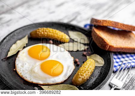 Fried Eggs In A Pan With Slices Of Black Bread And Pickled Cucumbers.
