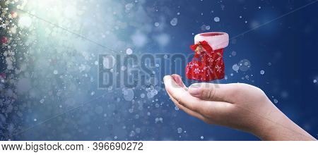 Christmas Concept: Hand Hold Christmas Shoes On Abstract Christmas Lights Background