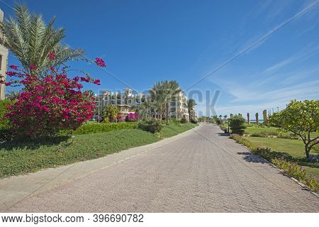 View Along A Footpath Walkway Through Beautiful Landscaped Gardens In Tropical Hotel Resort