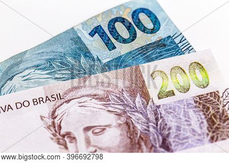 Banknotes Of 100 And 200 Reais, Money From Brazil. Concept Of Payment And Credit, Profit Or Wealth,