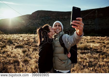 Young Adventurous Couple Taking Selfie With Smartphone While On Hiking Adventure During Sunset