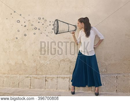young woman screams into a magaphone drawn in a wall
