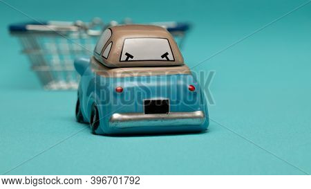 In-store Pickup. Toy Car And Shopping Cart On Blue Background. Selective Focus, Copy Space Of Your D