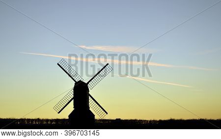 Windmill Silhouette At Sunset With Light Blue And Yellow Horizon With Wispy Light Pink Clouds At Sun