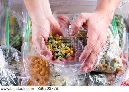 Frozen Green Beans In Hand, Closeup. Frozen Vegetables In A Plastic Bag In Freezer