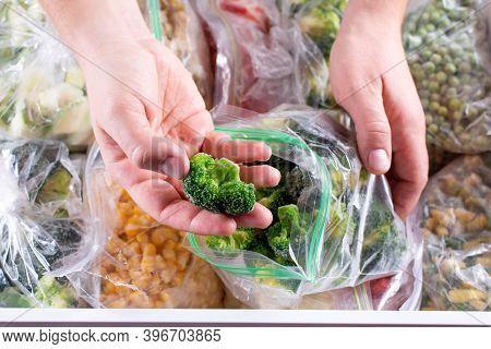 Frozen Broccoli In Hand, Closeup. Frozen Vegetables In A Plastic Bag In Freezer