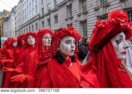 London, Uk - October 18, 2019: A Close Up Of Extinction Rebellion Red Brigade Protesters Parading In