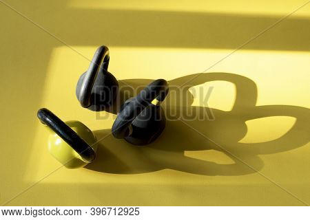 Three Kettlebells Staying On A Yellow Floor In The Gym. Kettlebells With Shadows. Sunny Day In Gym