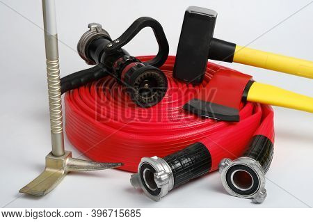 Red Rolled Fire Hose, Hooligan Pinch-bar, Large Yellow Sledgehammer And Axe From Firemans Toolbox On
