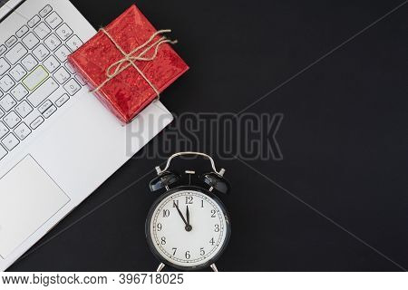 Black Friday Concept. Top View Of Alarm Clock, Red Giftbox And Laptop On Black Background, Copy Spac