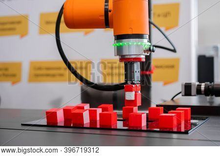 Orange Pick And Place Robotic Clamp Arm Manipulator Moving Red Toy Blocks At Modern Robot Trade Show