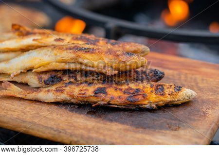 Crispy Breaded European Smelt Fish On Wooden Cutting Board At Summer Outdoor Food Market: Close Up.