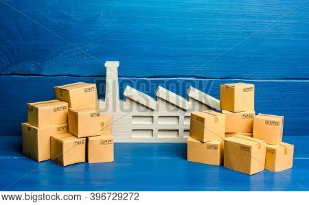 A Figurine Of A Plant And A Lot Of Boxes. The Concept Of Overproduction Of Goods. Overstocking Of Ma