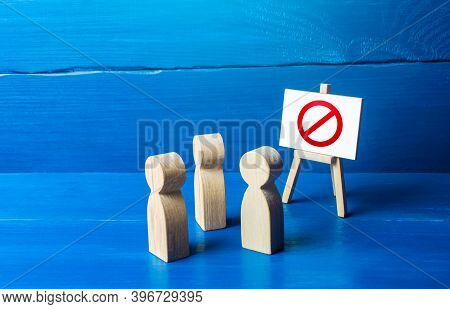A Group Of People Figurines Looking At An Easel With A Red Prohibitory Symbol No. Expression Of Prot