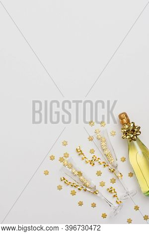 Festive White Background With Gold Decoration, Bottle Of Sparkling Wine With Two Crystal Glasses, Go