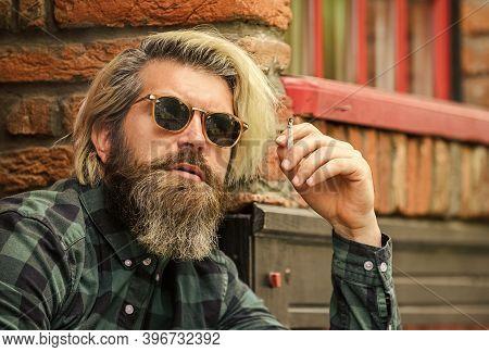 Man Smoking Outdoor. Fashionable Mature Man Smoking Cigarette. Punk Hipster Man Smoking. Smoking And