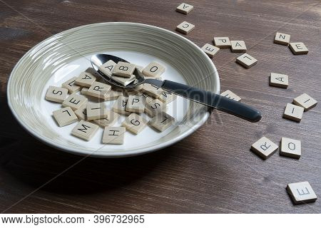 A Plate Full Of Letters On A Wooden Table