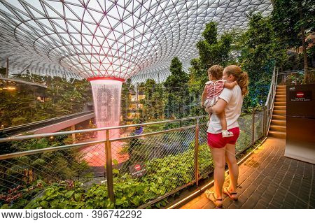 Singapore, Singapore - March, 4, 2020: Young Mother Holds Toddler Girl Travelers Looks At Waterfall
