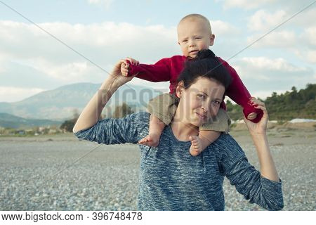 Routine Of Motherhood. Portrait Of A Young Tired Mother With A Baby In Her Arms While Walking. Fatig