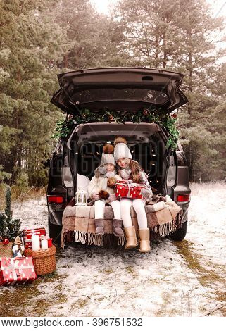 Preparation For Christmas. Teenage Children Enjoy A Christmas Gift In The Trunk Of A Car. Cold Winte
