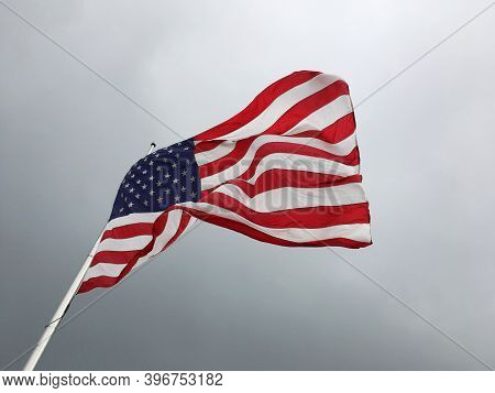 American Flag On The Background Of A Gloomy Sky. Flag Of The United States Flying Half Mast.