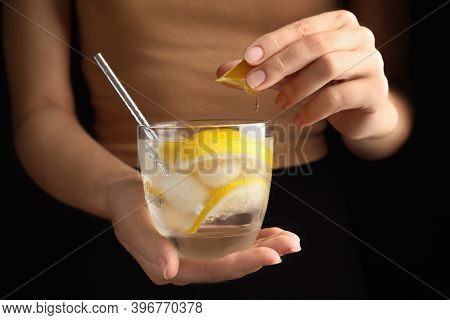 Woman Squeezing Lemon Juice Into Glass Of Soda Water With Ice Cubes, Closeup