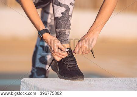 Close Up Of Slim Caucasian Woman Runner Tying Shoelaces. Preparing For A Run