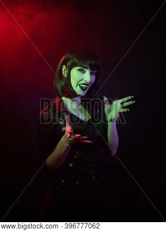 A Girl In The Guise Of A Vampire In A Green-red Light And Smoke Spread Her Arms And Looks Into The C