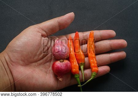Some Red Chilies And Shallots On The Palms Of Men
