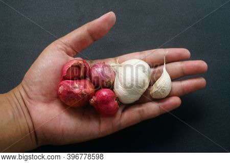 Some Shallots And Garlic On The Palms Of Men