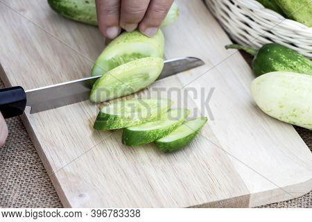 Women Holding Knife Cutting Slices Raw Cucumber Fresh On Wooden Cutting Board On Sackcloth Backgroun