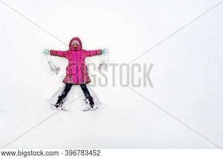 A Young Child Playing In The Snow Making An Angel. A Girl In A Red Jacket Plays In The Snow In Frost