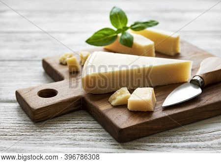Piece Of Parmesan Cheese On A Wooden Board