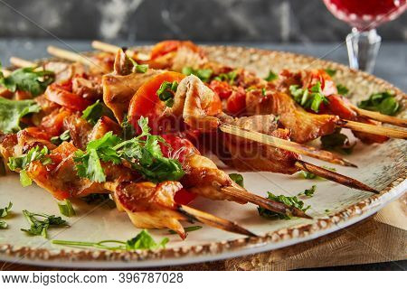 Japanese Style Yakitori Shashlik On A Wooden Board With A Glass Of Red Wine And Ginger. Close Up