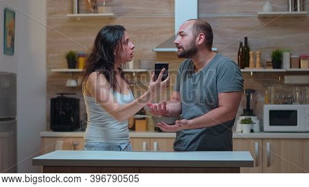 Wife Screaming At Unfaithful Husband In The Kitchen. Jealous Woman Cheated Angry Frustrated Offended