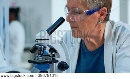 Woman Research Scientist Looking At Samples Under Microscope In Modern Equipped Laboratory. Eldery D