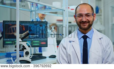 Portrait Of Scientist Man Smiling At Camera Sitting In Modern Equipped Laboratory. Multiethnic Team