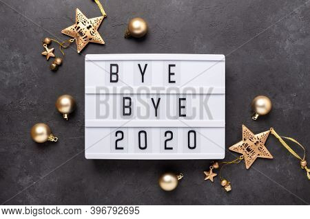 Lightbox With Text Bye Bye 2020 With Gold Decoration On Dark Background. Top View. New Year Celebrat