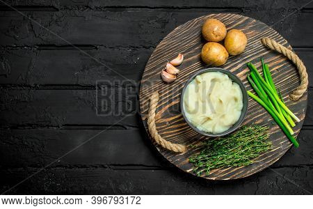 Mashed Potatoes In A Bowl With Herbs And Garlic. On A Rustic Background.