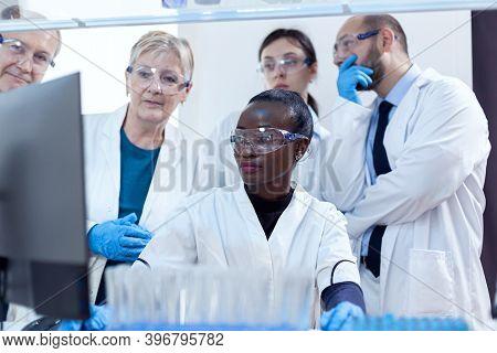 Group Of Scientists In Medicine Lab Looking At Computer Display Analysing Virus. Black Healthcare Re